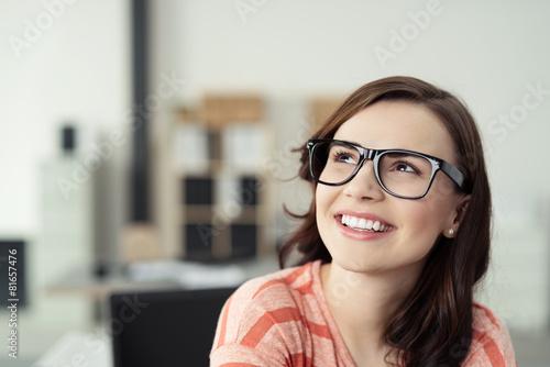 Leinwandbild Motiv zufriedene junge frau im büro schaut lächelnd nach oben