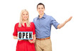 Young couple posing with an open sign