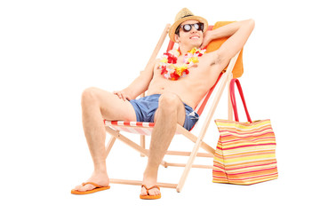 Relaxed man sitting shirtless in a sun lounger