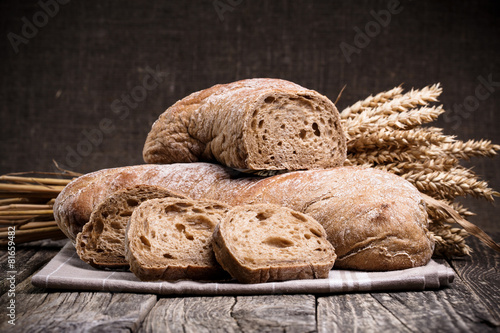 Fotobehang Brood Tasty bread with wheat on wooden background.