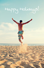 man jumping at beach - happy holidays