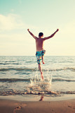 man jumping at beach - summer holidays
