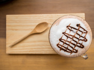 Hot coffee or chocolate served with milk foam and wooden saucer
