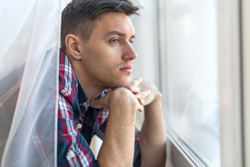Handsome pensive man guy watching through the window concept