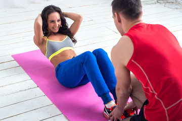 athletic sporty couple friends. Woman doing crunches abdominal