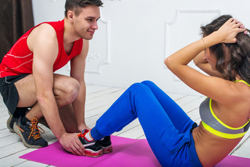 Man helping a woman or girl in making abdominal crunch