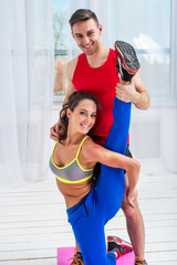 Young woman doing streching exercises with man smiling looking