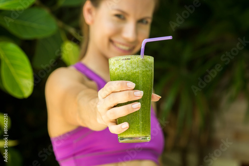Athletic girl holding a green smoothie - 81662251
