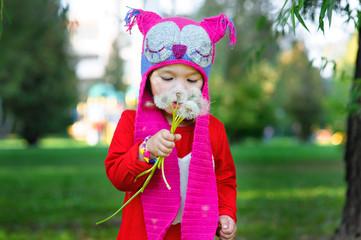 Little girl in the summer park holding a dandelion
