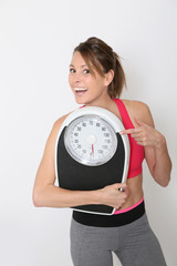 Cheerful girl in fitness holding scale, isolated