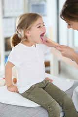 Doctor examining child's throat and mouth