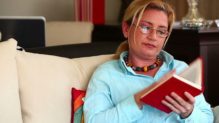Middle Age Housewife Reading a Book in Home
