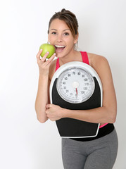 Cheerful girl in fitness outfit holding scale and green apple