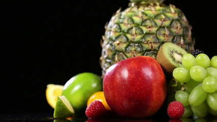 Fresh tasty fruits on black background