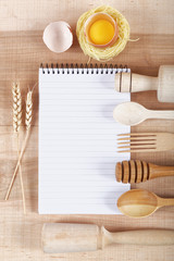 Baking ingredients for cooking and notebook for recipes on a woo