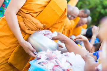 give alms to a Buddhist monk in Songkran Fest