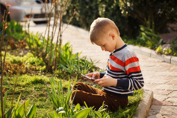 Young boy outdoors on the grass at backyard using his tablet com