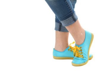 Blue sneakers on girl, young woman legs, isolated