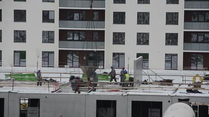builder pouring concrete new floor on construction site.