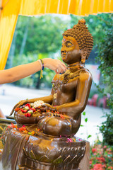 sprinkle water onto a Buddha image in Songkra festival