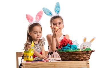 Two girls in kindergarten paint Easter eggs