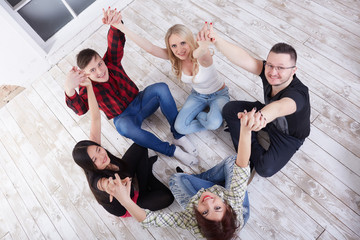 group of students in a bright room on the floor sit in a circle