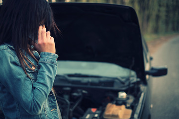 Woman with brown hair under the hood of her car break down