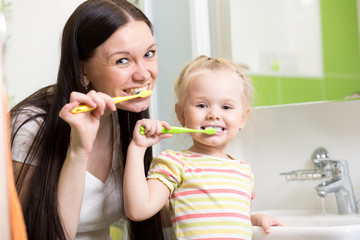 happy mother and daughter kid girl brushing teeth together
