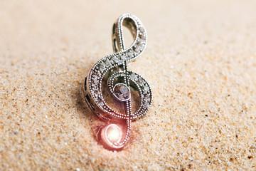 Violin key treble clef in sand