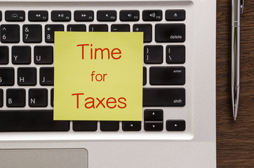 """Notepad with words """" Time for Taxes """" putting on laptop"""