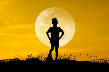 boy with soccer ball, big moon and grass silhouettes background