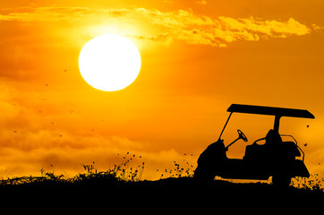 Golf cart on grass silhouettes background with sun set.