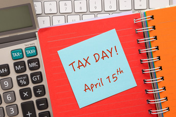 "Blue notepad with words "" TAX DAY "" on paper book"