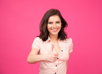 Smiling young woman showing thumb up