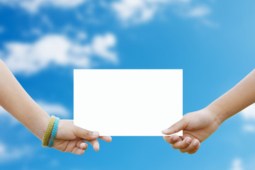 Two children holding a white paper background blur sky.