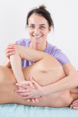 Woman therapist is doing massage on woman back