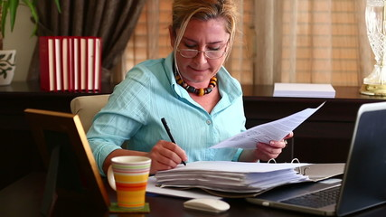 Middle Age Blonde Business Woman Signing Documents in Office