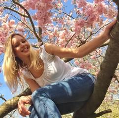Junge Frau sitzt im Kirschbaum