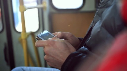 Close-up hands in bus man using his cell phone. Reading emails