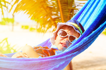 happy little boy relaxed in hammock on the beach