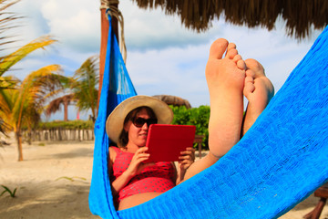 woman relaxing in hammockwith touch pad at the sea