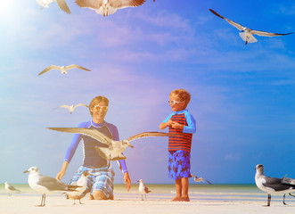 father and son feeding seagulls on the beach