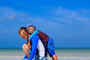 father and little son hug on summer beach