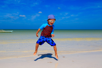 happy little boy jumping on sand beach