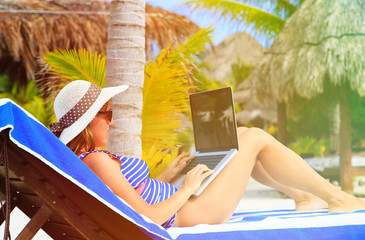 woman with laptop on tropical beach