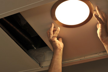 Electrician installing a light in the house
