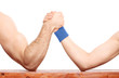 Arm wrestling between a muscular arm and skinny one