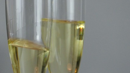 Swinging white wine in two glasses in slow motion