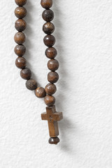 rosary beads  hanging against white wall