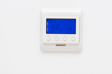 Plastic thermostat on a plain white wall